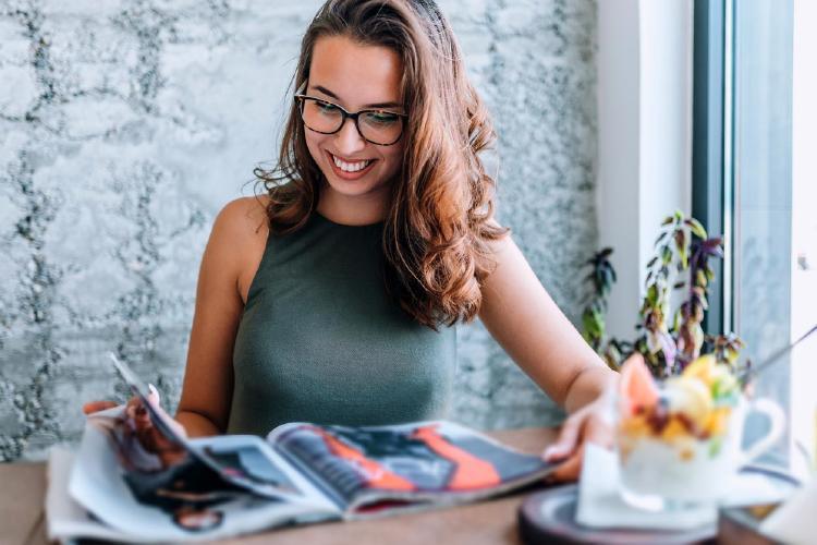 Mujer con gafas leyendo revista cerca de la ventana