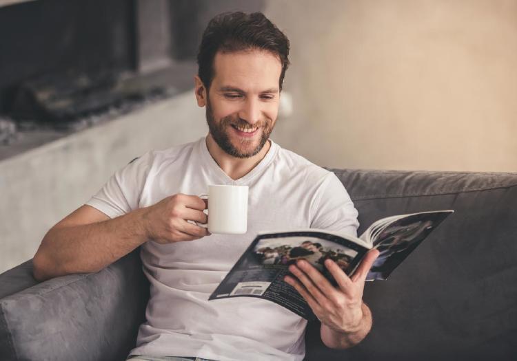 Hombre en casa leyendo un catalogo
